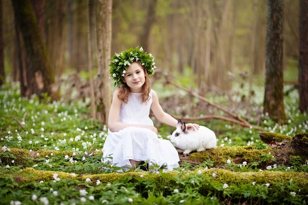 Piękna mała dziewczynka w białej sukni gra z białym królikiem w wiosennym drewnie. czas wielkanocy