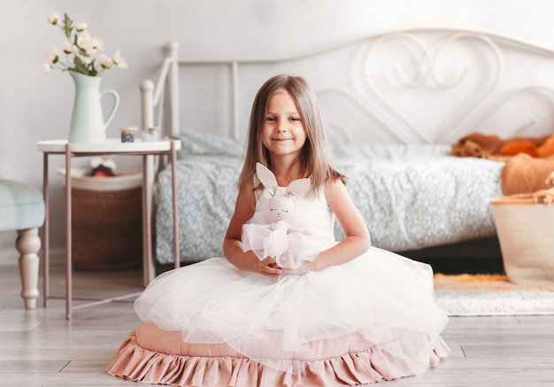 Piękna mała dziewczynka w białej sukni siedzi na podłodze w jasnym pokoju. patrząc na aparat. dzieciństwo.