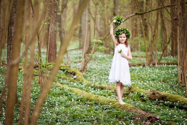Piękna mała dziewczynka w białej sukni spacery po wiosennym lesie. portret dziewczynki z wieńcem wiosennych kwiatów na głowie.