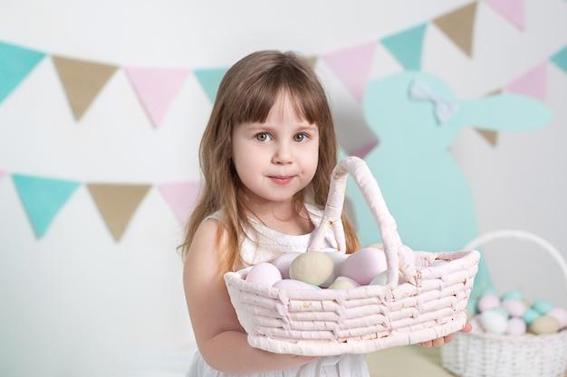 Piękna mała dziewczynka w białej sukni stoi z wielkanocnym koszykiem. wiele różnych kolorowych pisanek, kolorowe wnętrze. close-up portret twarzy dziecka. rolnictwo. dziecko i ogród.