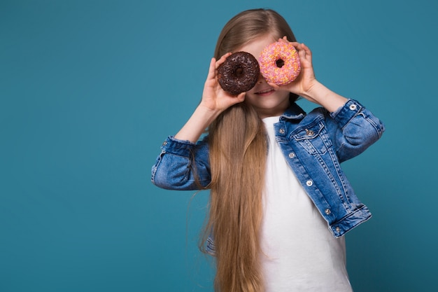 Piękna mała dziewczynka w cajgowej kurtce z długimi brązowymi włosami trzyma ciasto