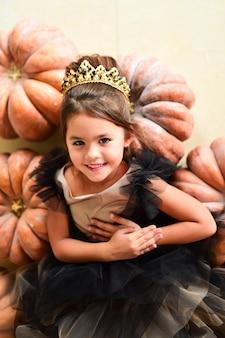 Piękna mała dziewczynka w czarnym wieczór gawn siedzi na pampkins w studiu