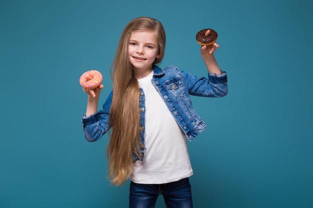 Piękna mała dziewczynka w dżinsowej kurtce z długimi brązowymi włosami trzyma ciasto