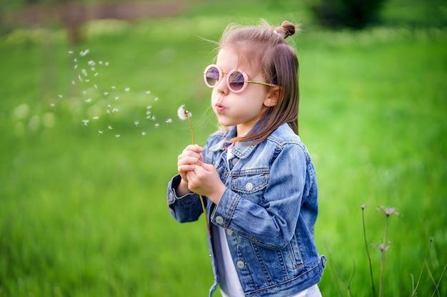 Piękna mała dziewczynka w dżinsowych ubraniach i zaokrąglonych okularach przeciwsłonecznych dmuchanie na mniszka lekarskiego na świeżym powietrzu w parku
