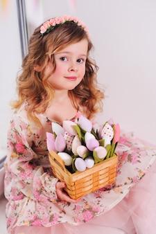 Piękna mała dziewczynka w eleganckiej sukni siedzi na parapecie z bukietem kwiatów tulipanów na powierzchni okna.
