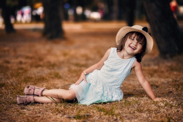 Piękna mała dziewczynka w kapeluszu i białej sukni dziewczyny siedzącej na trawniku