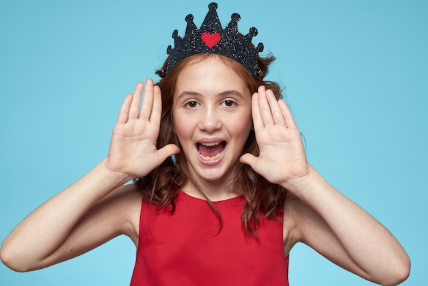Piękna mała dziewczynka w koronie, księżniczka, słodkie dziecko w studio na niebieskiej ścianie
