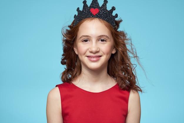 Piękna mała dziewczynka w koronie, księżniczka, słodkie dziecko w studio na niebieskim tle