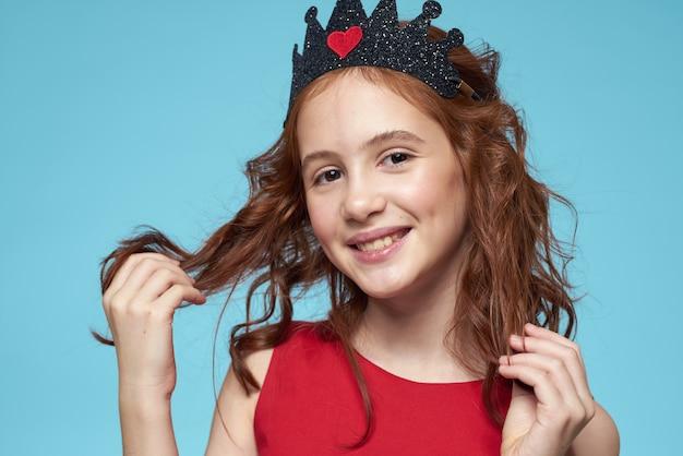 Piękna mała dziewczynka w koronie, księżniczka, słodkie dziecko w studio na niebiesko