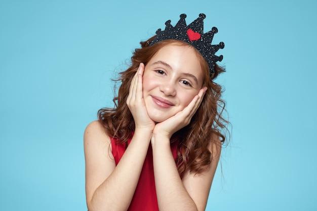 Piękna mała dziewczynka w koronie na niebieskim tle