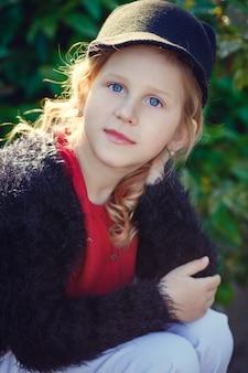 Piękna mała dziewczynka w ładny kapelusz z uszami w parku wieczorem.
