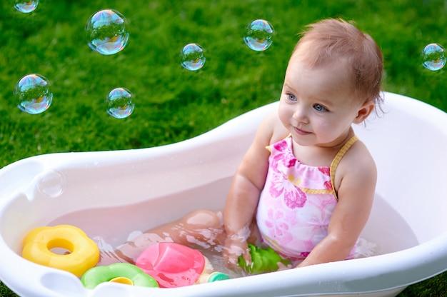 Piękna mała dziewczynka w lato kąpania zdroju z mydlanymi bąblami