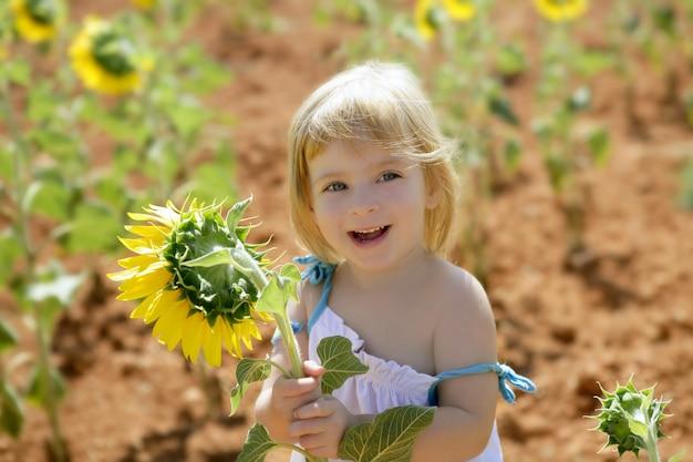 Piękna mała dziewczynka w lato słonecznikowym polu