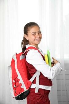 Piękna mała dziewczynka w mundurku szkolnym z plecakiem i książkami