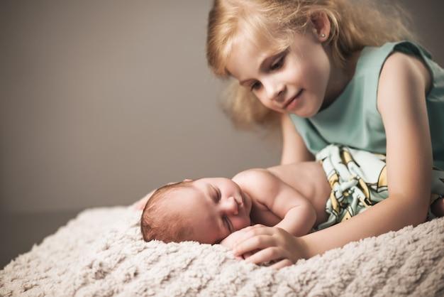 Piękna mała dziewczynka w niebieskiej sukience patrzy na swojego małego, czarującego śpiącego braciszka noworodka leżącego na kraciastej szarej ścianie. koncepcja uzupełnienia rodziny. copyspace