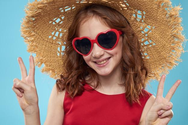 Piękna mała dziewczynka w okularach serca i czerwonej sukience, księżniczka, słodkie dziecko na niebiesko