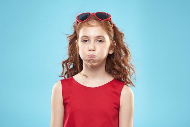 Piękna mała dziewczynka w okularach serca i czerwonej sukience, księżniczka, słodkie dziecko w studio na niebiesko
