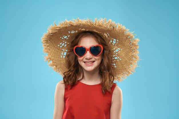 Piękna mała dziewczynka w okularach serca i słomkowym kapeluszu