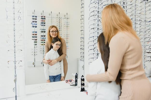Piękna mała dziewczynka w sklepie optycznym wraz z mamą wybierają nowe okulary