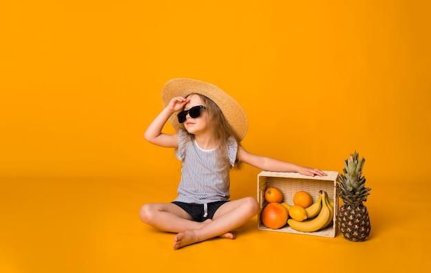 Piękna mała dziewczynka w słomkowym kapeluszu i okularach przeciwsłonecznych siedzi z koszem owoców na żółtej powierzchni i odwraca wzrok