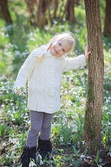 Piękna mała dziewczynka w słonecznym wiosennym lesie. polana przebiśniegów. czas wielkanocy.