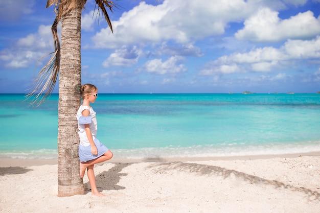 Piękna mała dziewczynka w sukni przy plażą ma zabawę.