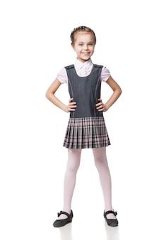 Piękna mała dziewczynka w szkolnym mundurku na białym tle