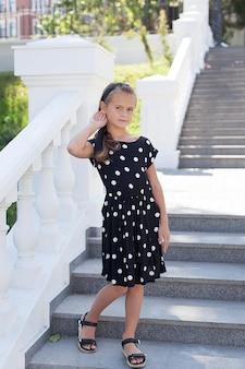 Piękna mała dziewczynka w wieku 8-9 lat w czarnej sukience w kropki stoi na pięknych białych schodach, uśmiechając się i patrząc w kamerę. letni nastrój.