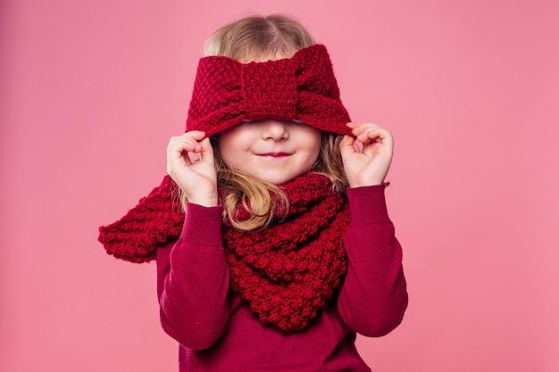 Piękna mała dziewczynka w zimie ciepły kolorowy czerwony kapelusz i szalik marzy noc bożego narodzenia grając w chowanego w studio na różowym tle. fotografia portretowa model dziecka ukrywający oczy pod czapką.