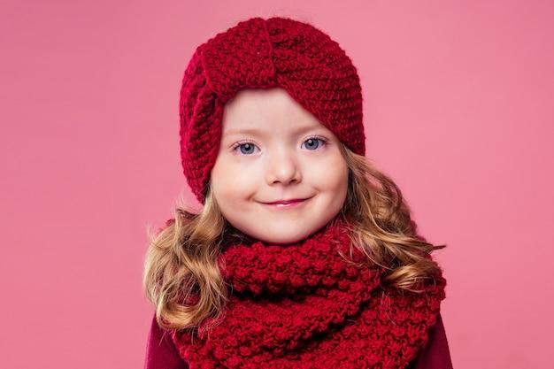 Piękna mała dziewczynka w zimowej ciepłej kolorowej czerwonej czapce i szaliku marzyła o prezencie noc bożego narodzenia w studio na różowym tle. fotografia portretowa model dziecka