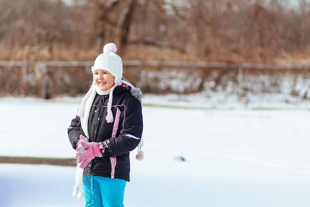 Piękna mała dziewczynka w zimowym parku mała dziewczynka spaceruje po parku w zimie