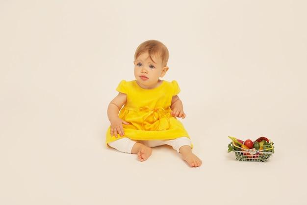 Piękna mała dziewczynka w żółtej sukience siedzi obok małego kosza z warzywami
