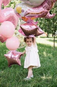 Piękna mała dziewczynka z balonami świętuje przyjęcia urodzinowego
