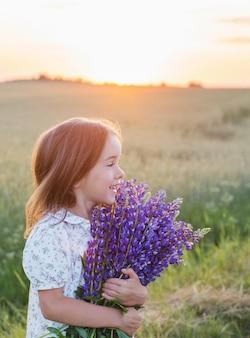 Piękna mała dziewczynka z bukietem kwiatów o zachodzie słońca