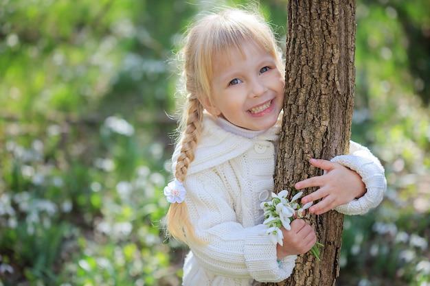 Piękna mała dziewczynka z bukietem przebiśniegów. mała dziewczynka w białym swetrze z dzianiny przytula pień drzewa. jasny słoneczny wiosenny dzień