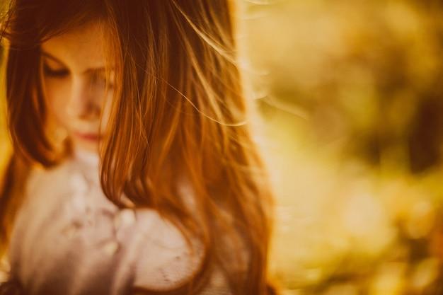 Piękna mała dziewczynka z czerwonymi włosami wygląda szczęśliwy grając z opadłych liści