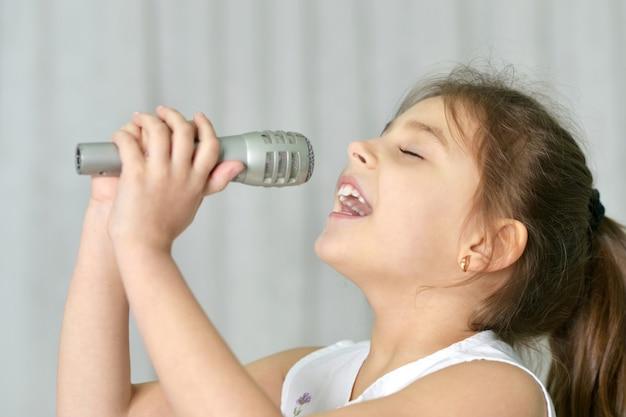 Piękna mała dziewczynka z mikrofonem w domu