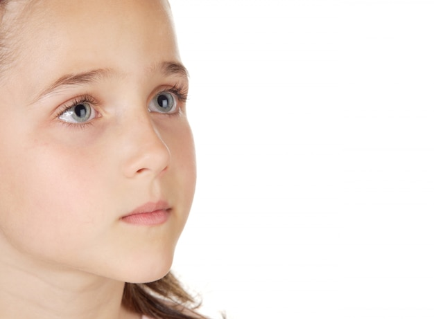Piękna mała dziewczynka z niebieskimi oczami patrząc na białym tle na białej przestrzeni