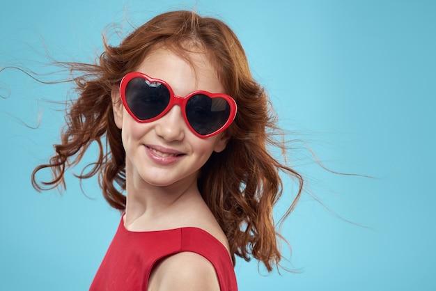 Piękna mała dziewczynka z okulary w kształcie serca na białym tle