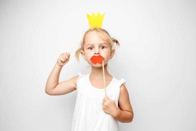 Piękna mała dziewczynka z papierową koroną i czerwonymi ustami pozowanie na białym tle w domu.