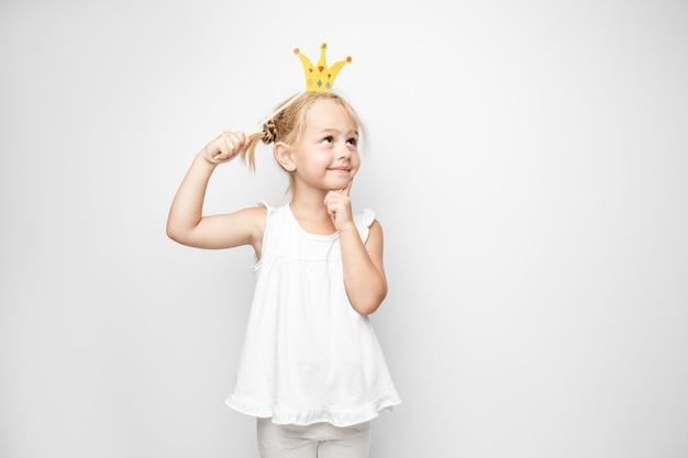 Piękna mała dziewczynka z papierową koroną pozuje na białym tle w domu