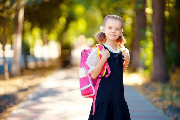Piękna mała dziewczynka z plecakiem spaceru w parku gotowy powrót do szkoły, jesień na zewnątrz, koncepcja edukacji.