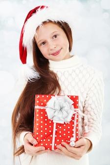 Piękna mała dziewczynka z prezentem na jasnej powierzchni
