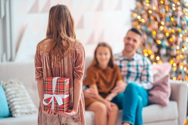 Piękna mała dziewczynka z prezentem. widok dziecka z tyłu trzyma pudełko w pobliżu choinki w pomieszczeniu. wesołych świąt i wesołych świąt.