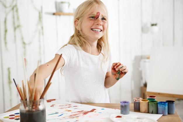 Piękna mała dziewczynka z prostymi blond włosami, piegami i farbą na twarzy, śmiejąca się i dobrze się bawiąca. zajęcia plastyczne dla dzieci.