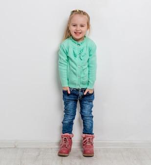 Piękna mała dziewczynka z rękami w kieszeniach