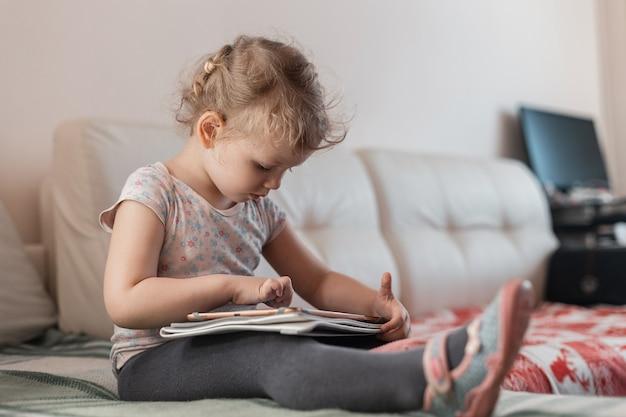 Piękna mała dziewczynka z tabletem, bawi się i siedzi na kanapie w domu. nauka na odległość i dziecko and