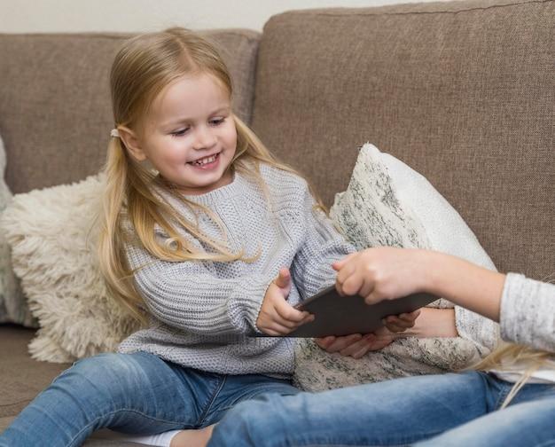 Piękna mała dziewczynka z tabletem w domu