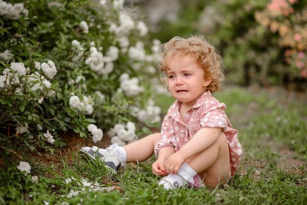 Piękna mała dziewczynka z uczciwym kędzierzawym włosy na spacerze w parku w ciepłym letnim dniu