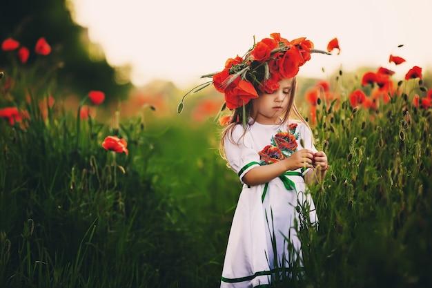 Piękna mała dziewczynka z wieńcem maków na głowie